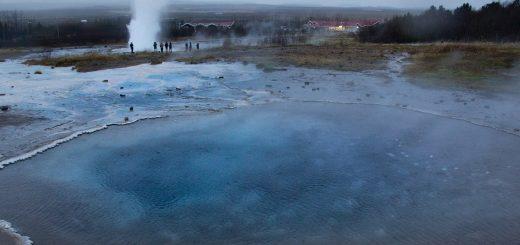 """Au premier plan le bassin d'eau bleue """"Blesi"""", qui réfléchit les paillettes de silice. Au second plan, le geyser Strokkur en éruption !"""