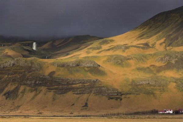 Paysage du sud de l'Islande qui illustre bien la météo : un ciel couvert mais un rayon de soleil qui illumine la montagne