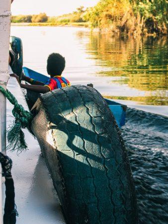 Enfant près d'une felouque sur le Nil à Assouan